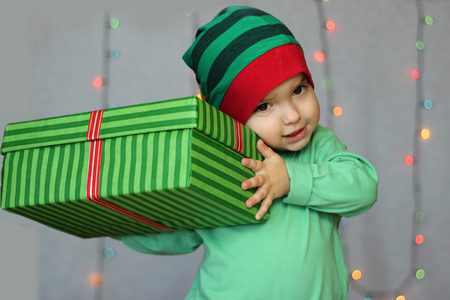 Portrait of happy little boy like elf holding a box with gift over Christmas background, winter holiday family concept