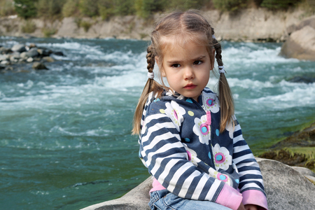 Pretty small girl with two braids sitting and dreaming on the bank of the mountain river in the Carpathians on a warm day, travel and active lifestyle, outdoor