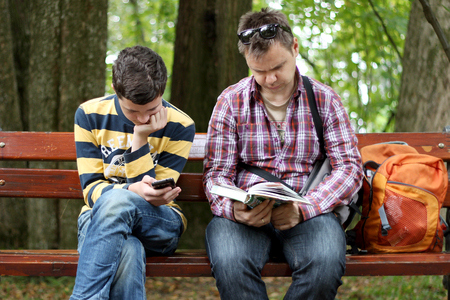 Middle aged man in black sun eyeglasses and checkered shirt reading a paper book near the teenager chatting with mobile phone, both are engaged, generation meeting concept, outdoor lifestyle