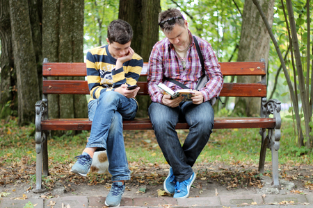 portative: Middle aged man in black sun eyeglasses and checkered shirt reading a paper book near the teenager chatting with mobile phone, both are engaged, generation meeting concept, outdoor lifestyle