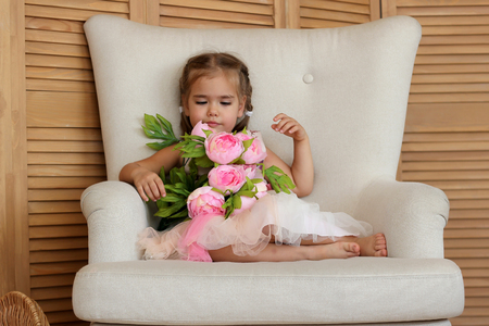 Portrait of pretty little girl in beautiful dress dreaming on the beige armchair with bouquet of pink roses, beauty and love concept, valentine and mother day