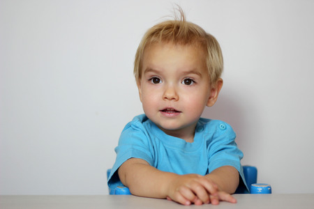 captivated: Handsome toddler boy in blue t-shirt with open mouth looking surprised over white background, child emotional portrait, indoor closeup  Stock Photo