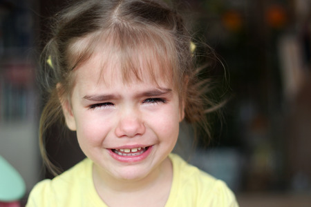 Cute preschooler blond girl crying and looking aside over dark background, emotional closeup portrait, upbringing and family concept