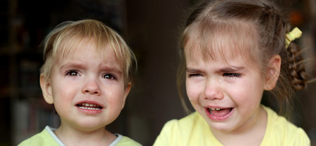 Two little children, boy and girl, crying over dark background, emotional closeup portrait, upbringing and family concept