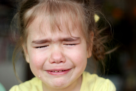 fussy: Cute preschooler blond girl crying with closed eyes over dark background, emotional closeup portrait, upbringing and family concept Stock Photo