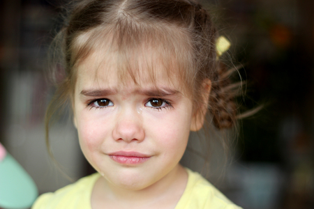 Cute preschooler blond girl crying and looking at camera over dark background, emotional closeup portrait, upbringing and family concept Stock Photo