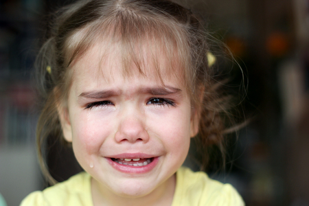 Cute preschooler blond girl crying and looking at camera over dark background, emotional closeup portrait, upbringing and family concept Banque d'images