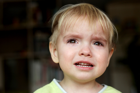 Pretty little blond boy crying over dark background, emotional closeup portrait, upbringing and family concept