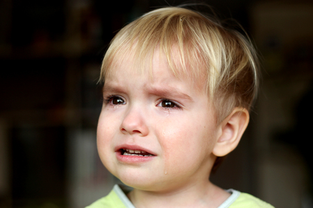Pretty little blond boy crying and looking aside over dark background, emotional closeup portrait, upbringing and family concept