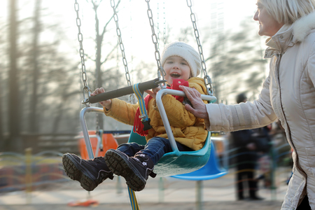 Smiling cute little girl having fun and flying on a chain swing carousel with her grandmother in the park, first sunny day in spring, happy family and childhood concept, outdoor closeup portrait Stock Photo