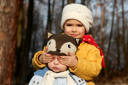 Pretty little girl and her cute smaller brother, she covered his eyes with her hands like during peek-a-boo game in a park at sunny day in spring, happy family concept, outdoor portrait