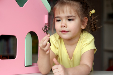 Cute girl kid playing with key in her hands near the doll house at home, indoor portrait, child activity, happy childhood concept Stock Photo
