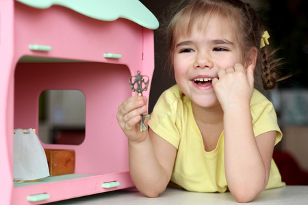 Cute girl kid playing with doll house at home, indoor portrait, child activity, happy childhood concept Stock Photo