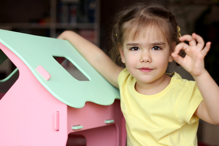 Cute girl kid playing with doll house at home and showing ok gesture, indoor portrait, child activity, happy childhood concept Stock Photo