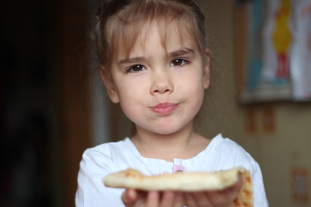 masticate: Beautiful hungry little girl sitting at table in the kitchen and eating a piece of pizza, food and drink concept, healthy childhood, indoor portrait