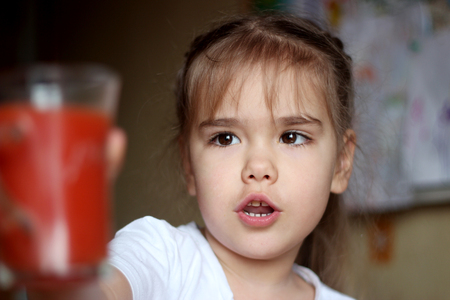 Portrait of gorgeous little girl reaching a glass of tomato juice at home, food and drink concept, healthy food, closeup indoor
