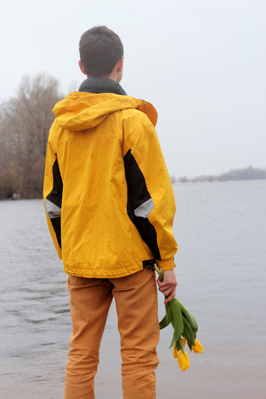 Handsome teenage boy in yellow coat with ear-phones and a bunch of yellow tulips waiting for a date on the bank of the river in a big city, outdoor portrait Stock Photo