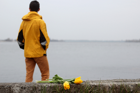 Young handsome teenage boy in yellow coat with ear-phones and a bunch of yellow tulips waiting for a date on the bank of the river in rainy day in a big city, outdoor portrait