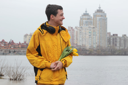 Young handsome teenage boy in yellow coat with ear-phones with a bunch of yellow tulips feeling happy while waiting for a date in rainy day in a big city, outdoor portrait