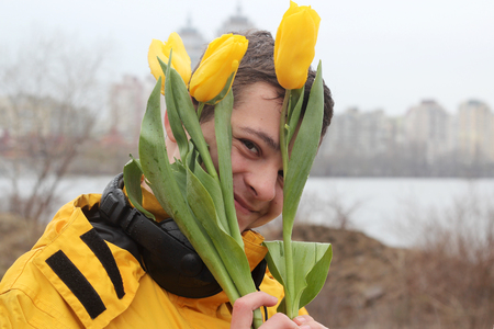 Young handsome teenage boy in yellow coat with ear-phones looking joyful through a bunch of yellow tulips and feeling happy in rainy day in a big city, outdoor portrait Stock Photo