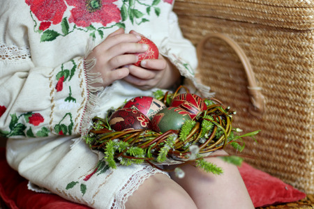 pascha: Cute girl in Ukrainian traditional embroidered dress and willow wreath holding decorated nest with colored Easter eggs, pysanky, Ukrainian history and culture, family holiday, focus on eggs in nest