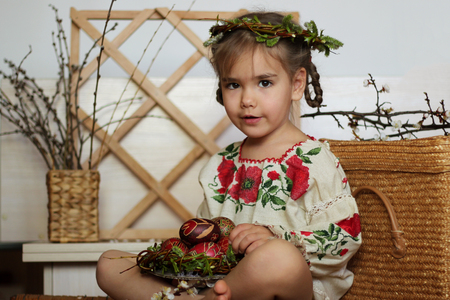 Cute smiling girl in Ukrainian traditional embroidered dress and willow wreath holding decorated nest with colored Easter eggs, pysanky, Ukrainian history and culture, happy family holiday, seasonal tradition