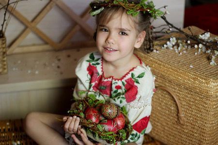 pascha: Cute girl in Ukrainian traditional embroidered dress and willow wreath holding decorated nest with colored Easter eggs, pysanky, Ukrainian history and culture, happy family holiday, seasonal tradition