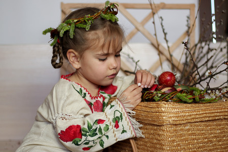 Cute girl in Ukrainian traditional embroidered dress and willow wreath holding decorated nest with colored Easter eggs, pysanky, Ukrainian history and culture, happy family holiday, seasonal tradition
