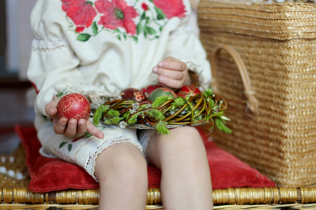 Cute girl in Ukrainian traditional embroidered dress and willow wreath holding decorated nest with colored Easter eggs, pysanky, Ukrainian history and culture, family holiday, focus on hand with egg