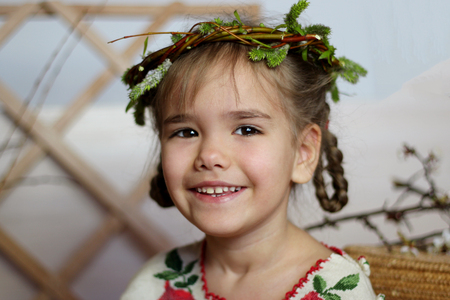 Cute girl in traditional embroidered dress and willow wreath stays leaning on the wooden wall, dreamily look, Ukrainian history and culture, happy family holiday, closeup indoor portrait