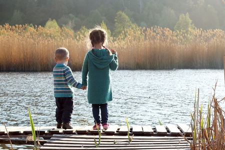 Beautiful toddler boy and his cute sister standing together on the wooden pier by the lake in the forest at sunny spring day, happy family weekend, lifestyle outdoor, back view