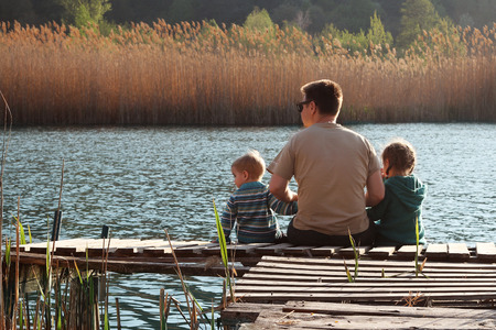 Beautiful toddler boy and his cute sister sitting together with their father on the wooden pier by the lake in the forest at sunny spring day, happy family weekend, lifestyle outdoor, back view Stock Photo
