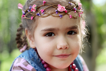 Close-up portrait of little beautiful blonde girl wearing an elegant wreath of leaves and flowers posing in a green meadow. Fashionable attractive child, gorgeous fair hair female, outdoor summer shot