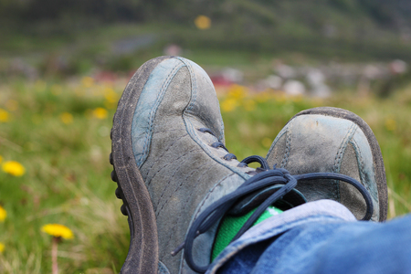 Legs with old blue trekker shoes over blurred green meadow background, healthy lifestyle, active vacations concept, summer outdoor, Carpathian Mountains Stock Photo