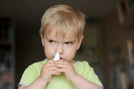 Cute 2 years old toddler boy spraying medicine in nose against flu, nose drops, nose spray, health and care concept, doctor and self-medicating