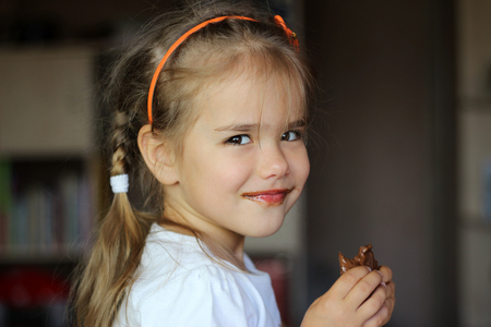 Pretty smiling girl dirty with chocolate eating it with pleasure, food and drink concept, chocolate face, indoor emotional portrait