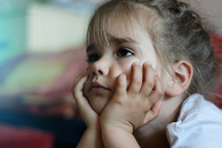 A cute little girl is lying on the sofa with hands on chin and boring in the light of tv screen, emotional portrait, television and internet influence