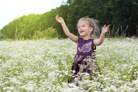 Cute little girl wearing beautiful dress meets sun with hugs among chamomile field, beauty and fashion, happy childhood, summer vacation, outdoor