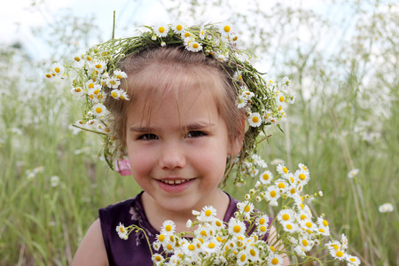 Cute funny little girl in wildflower wreath with huge bouquet of white flowers staying in chamomile field, beauty and health care, happy childhood, active summer vacation, close-up outdoor portrait