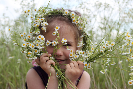 Little girl in wildflower wreath is hiding at bouquet of white flowers in chamomile field, beauty and health care, happy childhood, active summer vacation, close-up outdoor portrait, focus on flowers