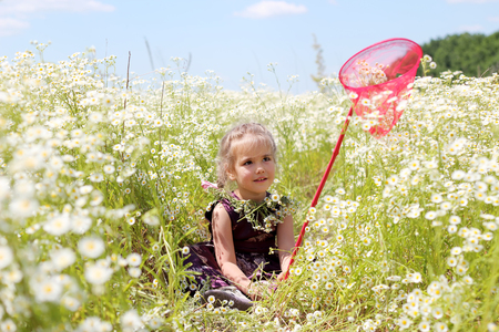 Cute funny little girl with wildflower wreath on her neck and butterfly net sitting tired in chamomile field, beauty and health care, happy childhood, active summer vacation, close-up outdoor portrait