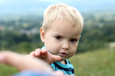 Cute little boy stretches out his arm to catch somebody with one hands, summer outdoor, beautiful nature sight background, gesture and sing concept