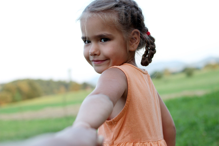 Cute happy preschool girl stretches out her arms to make go somebody for playing, summer outdoor, beautiful nature sight background, gesture and sing concept