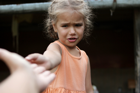 Attractive crying preschooler girl stretches out her arm to ask for help somebody, summer outdoor, dark background, gesture and sing concept