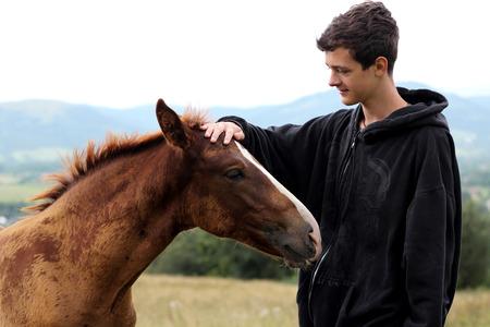 Joven durante el montaje de alto se encuentra un caballo joven y se comunica con él, la naturaleza salvaje, la gente y los animales concepto de amistad, el estilo de vida de verano al aire libre Foto de archivo - 85531403