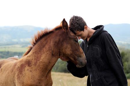 Jeune garçon pendant la marche, rencontre un jeune cheval et communique avec lui, nature sauvage, concept d'amitié entre humains et animaux, style de vie estival en plein air