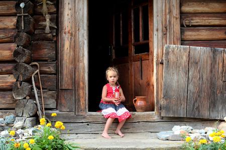 Aantrekkelijk jong meisje zit op de drempel van het plattelandshuis en houdt een aardewerkpotje met organische melk, zomer openlucht, gezond levensstijlconcept