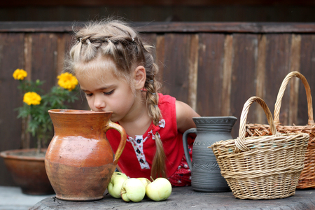 non: Attractive young girl sitting before wicker baskets, green apples and earthenware pot with organic milk, countryside background, summer outdoor, healthy lifestyle concept