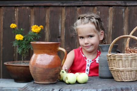 Aantrekkelijk jong meisje zitten voor rieten manden, groene appels en aardewerk pot met biologische melk, platteland achtergrond, zomer openlucht, gezond levensstijl concept