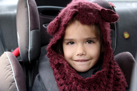 Close-up portrait of cute white little girl wearing fashion knitted purple hat and sitting in the child safety seat in the car, autumn outfit, child safety, family travel